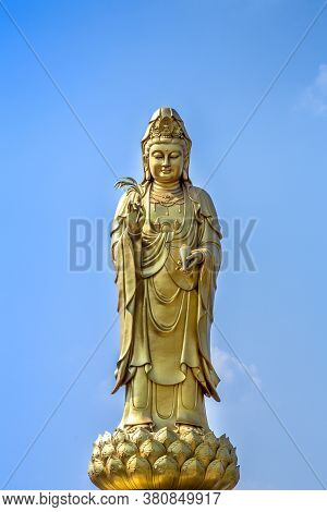 Golden Statue Of The Goddess Of Mercy  Guanyin Or Guan Yin Standing On The Lotus On Blue Sky Backgro