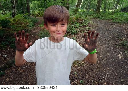 Young Boy In Clean White Shirt, But Very Muddy Hands After Playing In The Woods