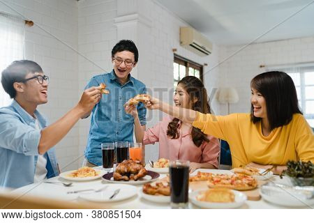 Happy Young Friends Group Having Lunch At Home. Asia Family Party Eating Pizza Food And Laughing Enj