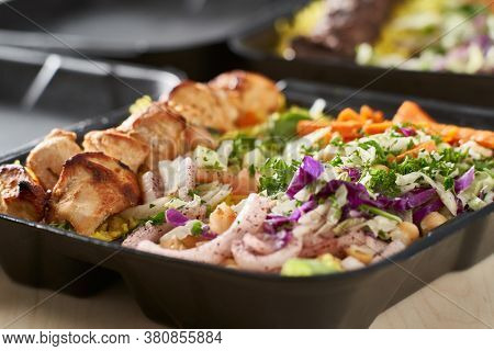greek chicken souvlaki take out container with rice and pickled vegetables