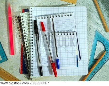 Notepads, Notepads, Pens, Pencils, Rulers And Other Office Supplies On A Green Table Surface. Backgr