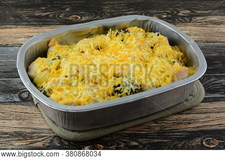 Chicken Potato And Broccoli Casserole With Shredded Cheese Topping In Foil Baking Pan On Potholder O