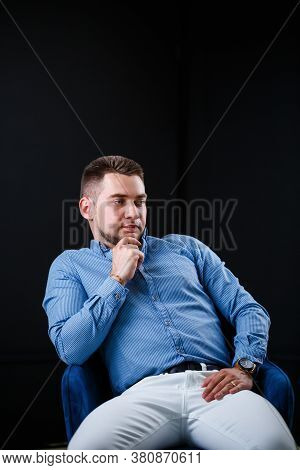 Fellow Businessman In Blue Shirt And White Trousers On A Black Background