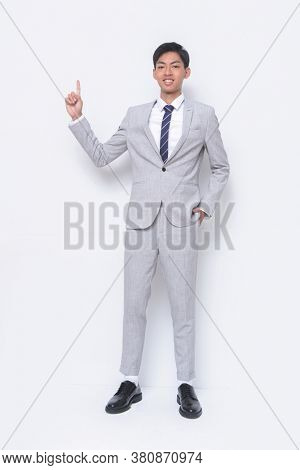 full length young handsome businessman   man wearing in gray suit ,tie with white shirt and gray pants with black shoes with finger pointing up.