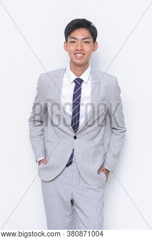 young handsome businessman   man wearing in gray suit ,tie with white shirt and gray pants with hands holds pockets standing