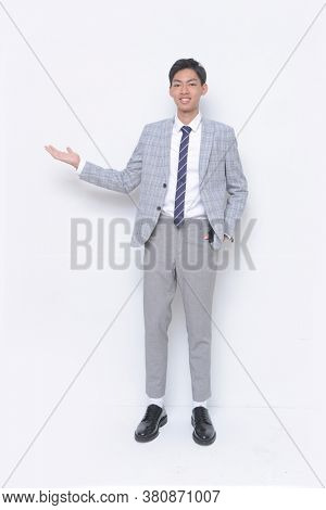 full length young handsome man wearing in striped gray suit ,tie with white shirt and gray pants , black shoes standing handshake as greeting and welcoming