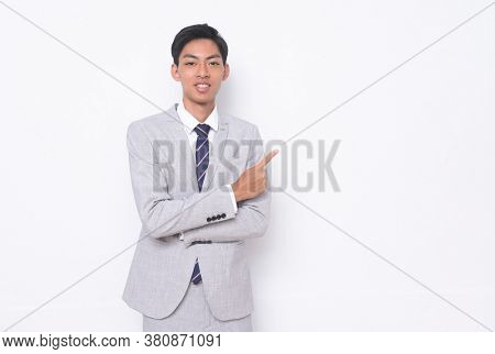 young handsome businessman wearing in gray suit ,tie with white shirt and gray pants with pointing finger to side