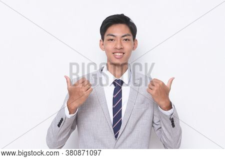 young handsome businessman  wearing in gray suit ,tie with white shirt doing ok sign, thumb up