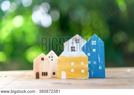 Closed Up Tiny Home Model On Floor Or Wood Board With Sunlight Green Bokeh Background. House Propert