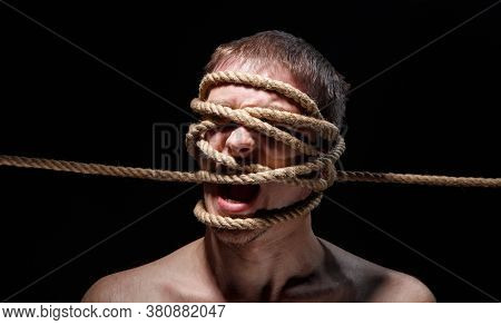 Photo Of Binded Screaming Man With Rope On Face