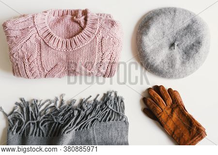 Flat Lay With Handmade Knitted Sweater, Beret Hat, Woolen Scarf And Suede Gloves On White Background