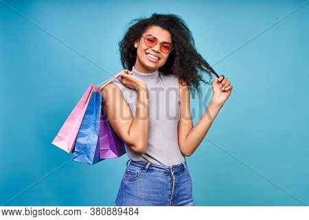 Attractive Young Dark Skinned Woman With Sincere Happy Smile Holding A Bunch Of Shopping Bags Isolta