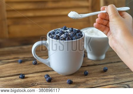 Close Up View Of A White Cup Full Of Fresh Shadberry And A Cup Full Of Sugar On An Old Grunge Wooden