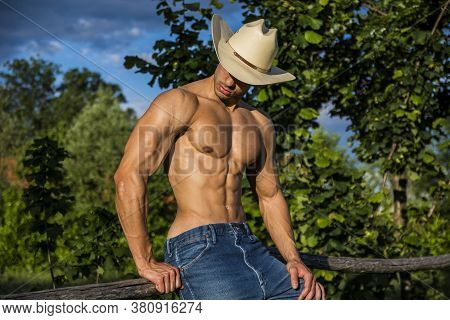 Sexy Farmer Or Cowboy Next To Hay Field