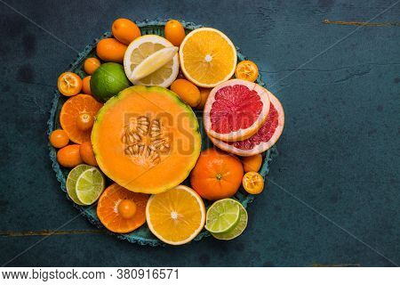 Flat lay layout of fruit citrus and other sommer fruits on green background. Healthy eating concept.