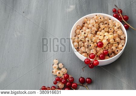 Red And White Currants On A Dark Background. White Cup With White Currants. The View From The Top. P