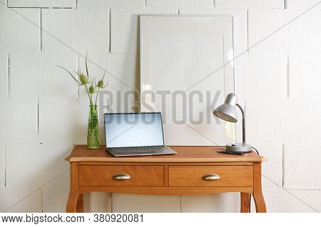 Small Vintage Table Of Reddish Wood With Laptop, Desk Lamp And A Picture Frame In Front Of A Raw Whi