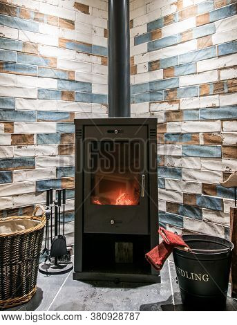 Modern Wood Burning Stove. Tiled Wall Behind, Stove With Fire Burning Inside, Cosy And Warm Interior