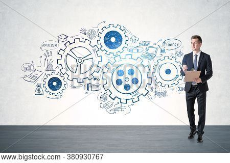 Young Businessman With Clipboard Walking In Concrete Room With Gears Sketch Drawn On The Wall. Conce