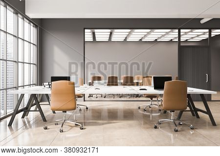 Interior Of Stylish Open Space Office With Gray Walls, Concrete Floor, White Computer Tables And Mee