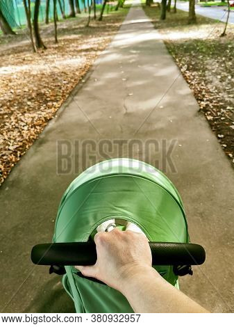 Hand Holding The Handle Of A Baby Stroller With On A Walk In Autumn Park. Walk With A Child In A Str