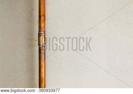 Close Up Shot Of A Copper Pipe Newly Repaired On Stucco Wall Background, Lots Of Copy Space For Your