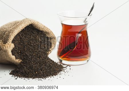 Glass Turkish Brewed Black Tea And Dry Black Tea In Burlap Sack Isolated On White Background. Turkis