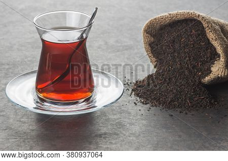 Glass Turkish Brewed Black Tea With Dry Black Tea In Burlap Sack On Black Rustic Background. Turkish