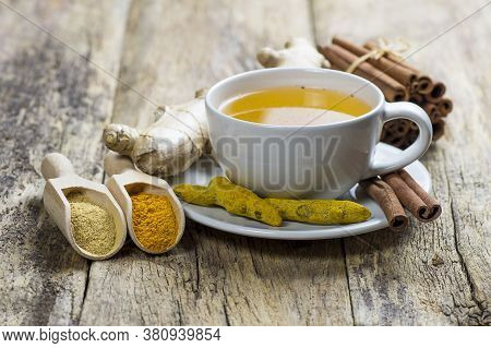 Herbal Ginger And Turmeric Tea In White Cup With Ginger Root, Dry Turmeric, Cinnamon Sticks And Thei