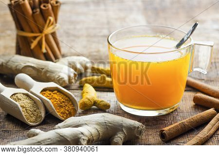 Herbal Ginger And Turmeric Tea In Glass Cup With Ginger Root, Dry Turmeric, Cinnamon Sticks And Thei
