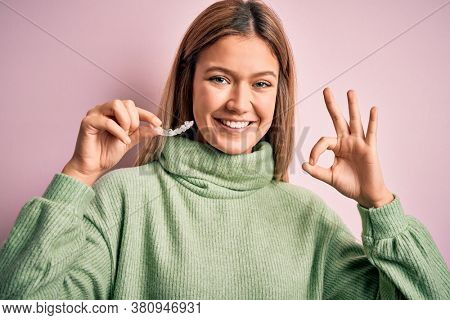 Young beautiful woman holding aligner standing over isolated pink background doing ok sign with fingers, excellent symbol