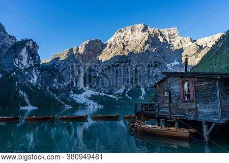 Panoramic View Of Braies Lake With The Hut And Boats In Dolomites Mountains And Seekofel In The Morn