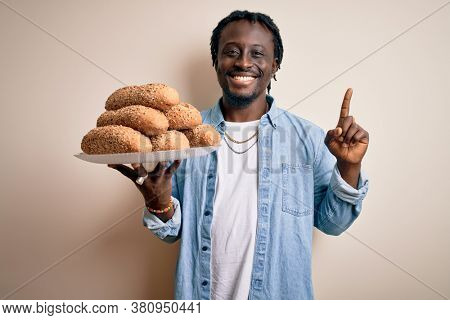 Young african american man holding tray with healthy wholemeal bread over white background surprised with an idea or question pointing finger with happy face, number one