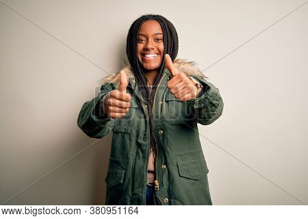Young african american woman wearing winter parka coat over isolated background approving doing positive gesture with hand, thumbs up smiling and happy for success. Winner gesture.