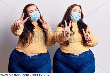 Young plus size twins wearing medical mask smiling looking to the camera showing fingers doing victory sign. number two.