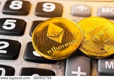 Golden Ether Coins Or Ethereum Network Exchange On Calculator Background, Blockchain And Money Crypt