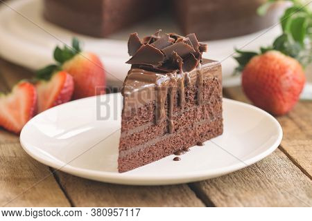 Fresh Baked Layers Sponge Chocolate Cake On White Plate With Chocolate Curl And Sauce On Wood Table.
