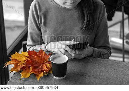 Median Age Woman In  Cafe Whriting Text Message From Her Mobile Phone. Autumn Still Life With Cappuc