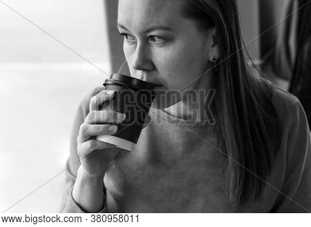 Portrait Of Median Age Woman Drinking Coffee In Cafe Close Up. Looks Pensively Out The Window