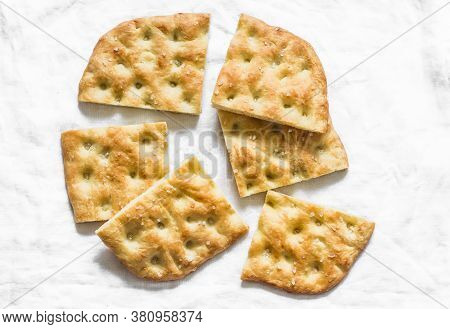 Italian Focaccia On A Light Background, Top View. Traditional Italian Bread