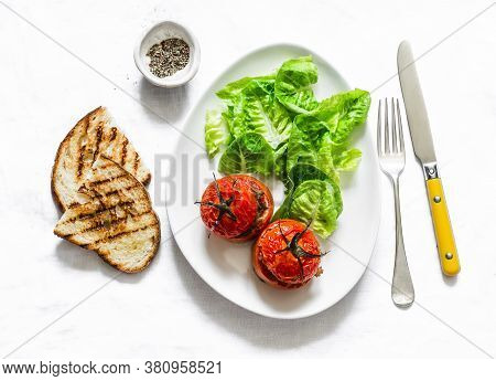Delicious Appetizers, Tapas - Stuffed Roasted Tomatoes, Lettuce And Grilled Bread On A Light Backgro