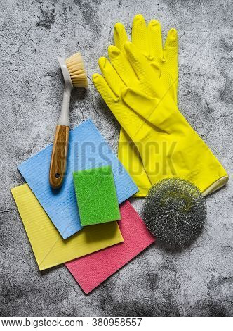 Home Cleaning Equipment - Rubber Gloves, Sponges, Brushes, Rags On A Gray Background, Top View. Copy