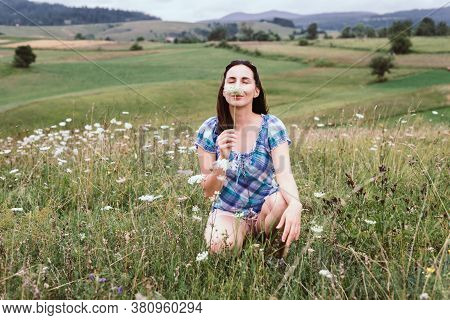 Beautiful Woman Smelling Flowers In Nature. Happy People Lifestyle. Woman Smelling Flowers In Meadow