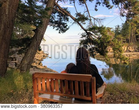 A Mother And Young Daughter Sitting Side By Side On A Bench Overlooking The Ocean On A Beautiful Eve