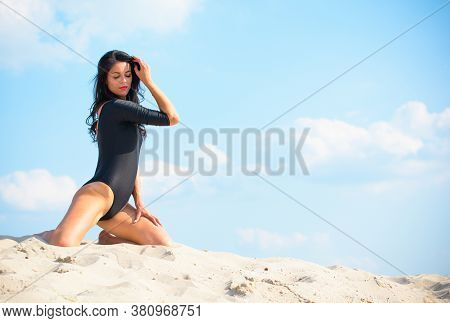 A Young Woman In Tights Is Engaged In Gymnastics On The Sand, Trains, Behaves In Good Shape. Pleasur