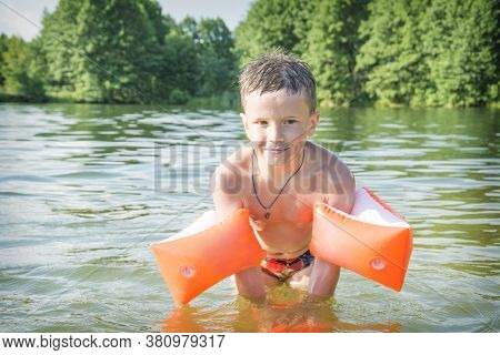 In Summer, On A Bright Sunny Day, A Boy In Inflatable Armbands Swims In The Lake.