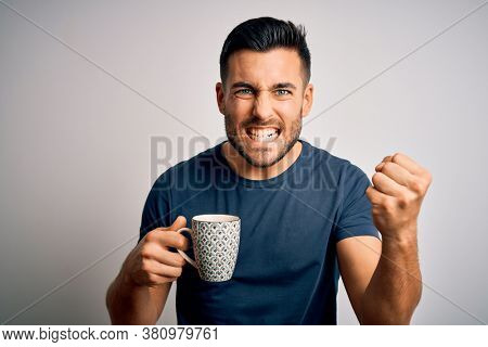 Young handsome man drinking a cup of hot coffee over white isolated background annoyed and frustrated shouting with anger, crazy and yelling with raised hand, anger concept