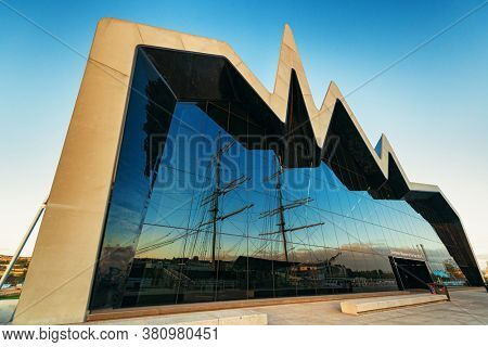 GLASGOW, UK - FEB 26, 2020: Riverside Museum of Transport and Travel with vintage sail ship at sunset