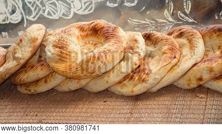 Typical Traditional Flatbread With Crunchy Crust With Sesam Just Baked In Tandoor On Market Display