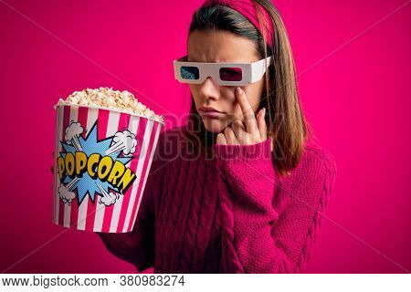 Young beautiful girl watching movie using 3d glasses eating box with popcorns Pointing to the eye watching you gesture, suspicious expression
